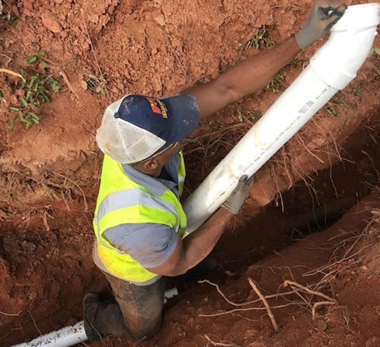 man repairing sewer drain for homeowners